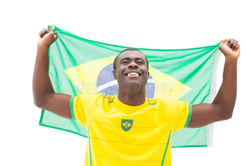 Fan de futebol brasileiro feliz que cheering guardando a bandeira foto de stock
