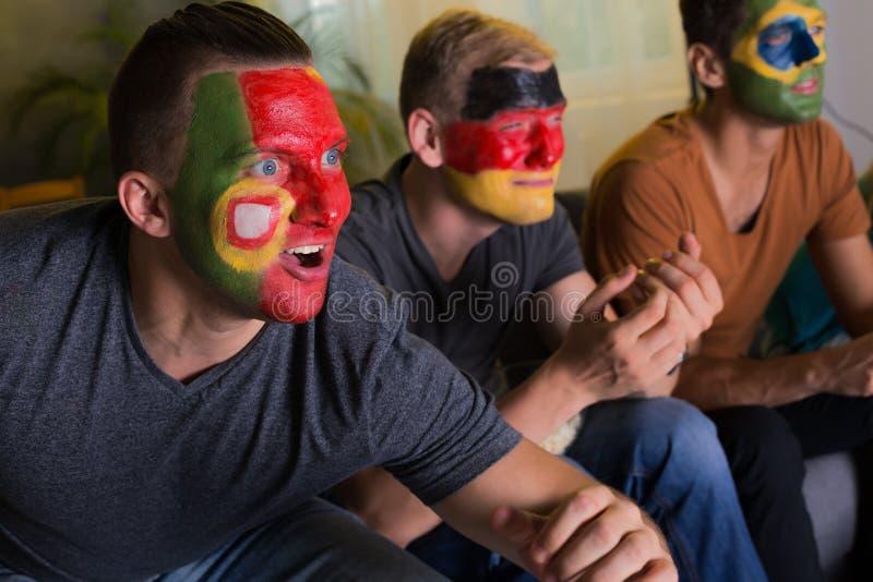 Fan de futebol entusiasmado com caras coloridas foto de stock