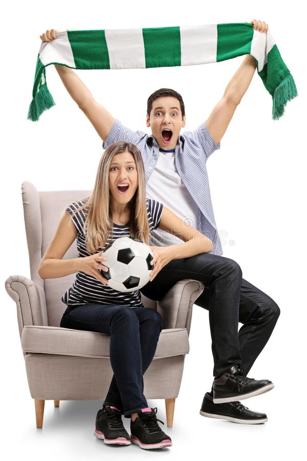 Fan de futebol entusiasmado que sentam-se em uma poltrona e em um cheering imagens de stock