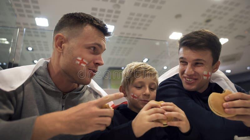 Fan de futebol ingleses que comem hamburgueres após o fósforo, efeito prejudicial do fast food fotos de stock royalty free