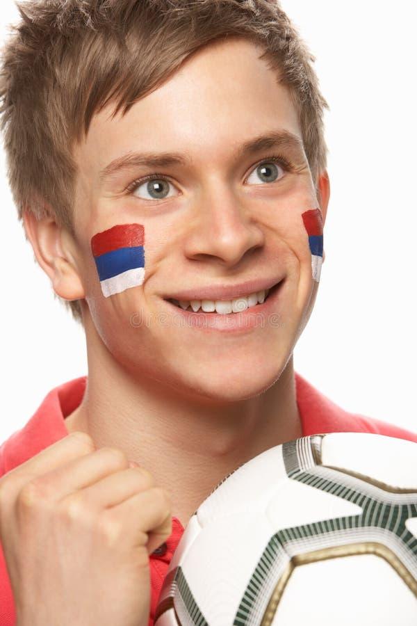Fan de futebol masculino novo com a bandeira sérvio pintada fotografia de stock royalty free