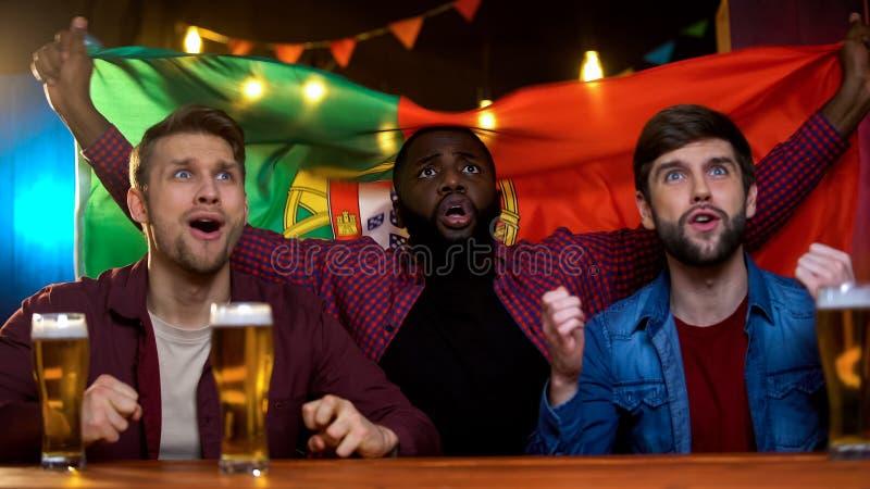 Fan de futebol multirraciais ansiosos com resultados de espera do fósforo da bandeira portuguesa fotografia de stock