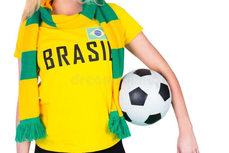 Fan de futebol no tshirt de Brasil que guarda a bola imagem de stock royalty free