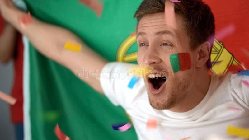 Fan de futebol de Portugal que comemora o objetivo de vencimento, jogo de futebol de observação na tevê foto de stock royalty free