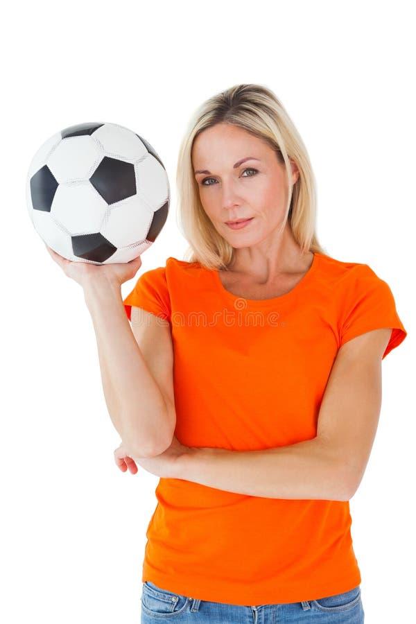 Fan de futebol que guarda a bola no tshirt alaranjado foto de stock royalty free
