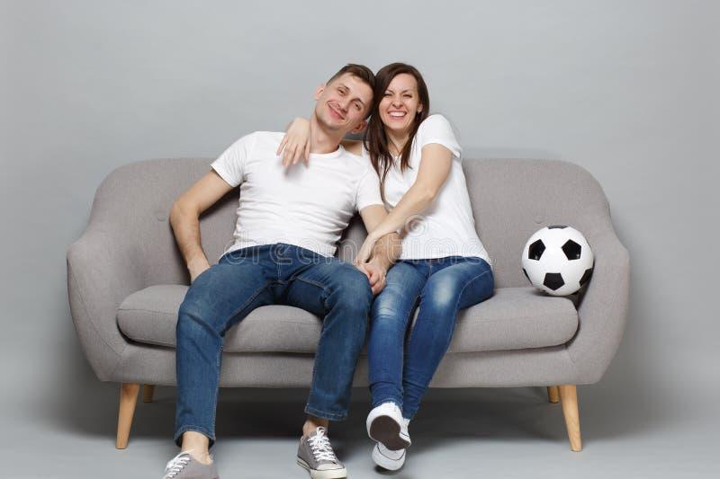 Fan de futebol de sorriso do homem da mulher dos pares no elogio branco do t-shirt acima da equipe favorita do apoio com a bola d imagem de stock royalty free