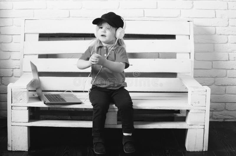 Fan de música novo o rapaz pequeno nos auriculares escuta música, audiobook, trabalhando em portáteis imagem de stock royalty free