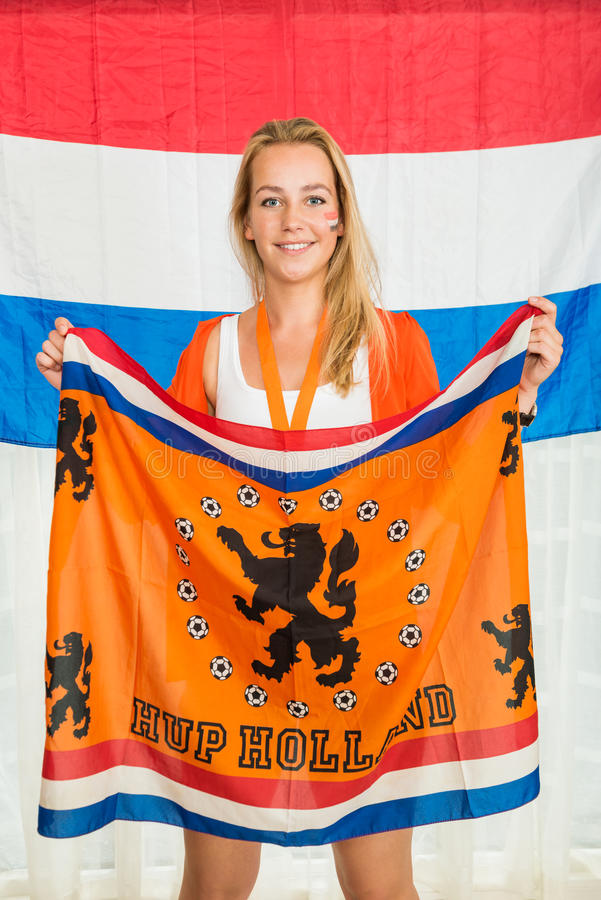 Fan de sports néerlandaise tenant le drapeau encourageant devant Holland Flag photos stock