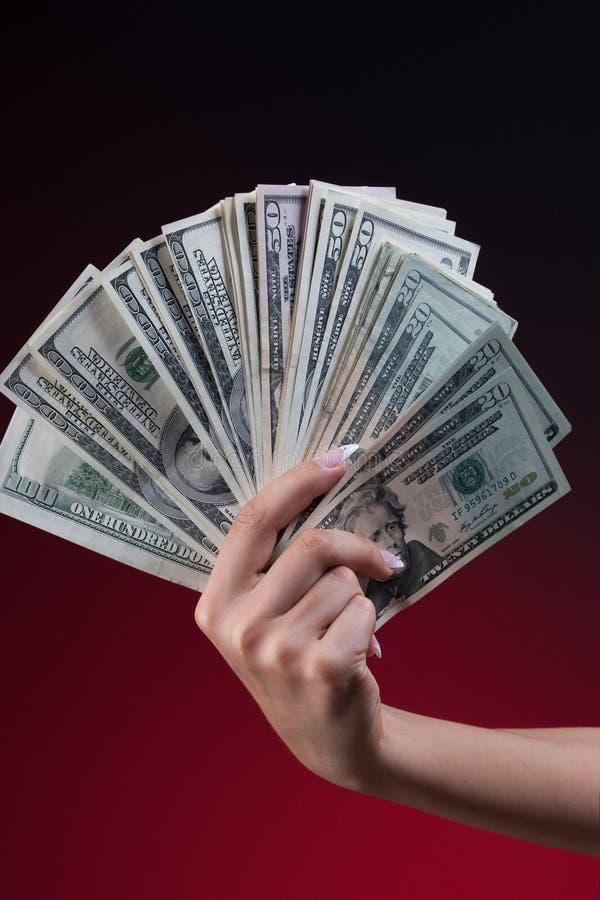 Fan della tenuta della mano della mano della donna dei dollari immagine stock