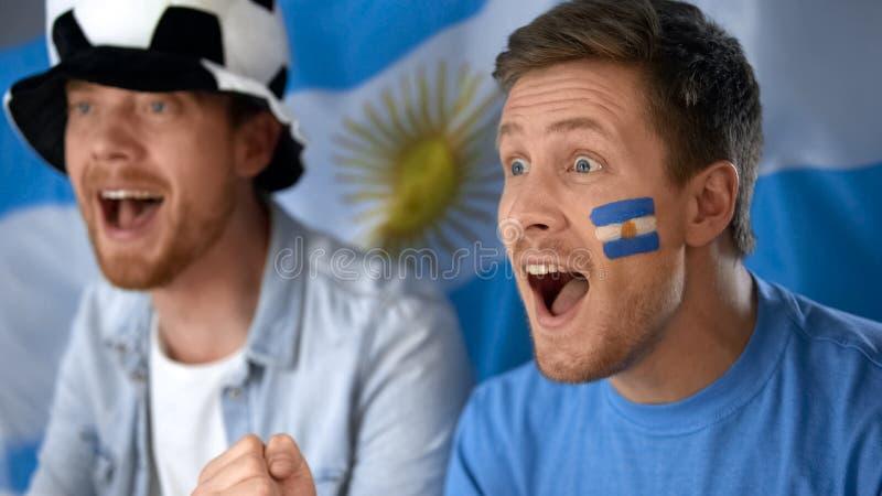 Fan di calcio dell'Argentina che guardano partita di football americano sulla TV, celebrante vittoria del gruppo fotografia stock libera da diritti