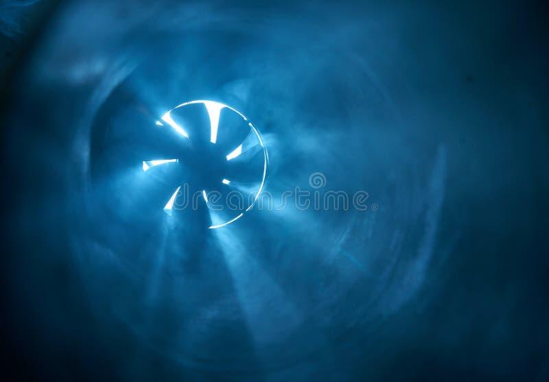 Fan exponerad av strålar av ljus i mörkret arkivbild