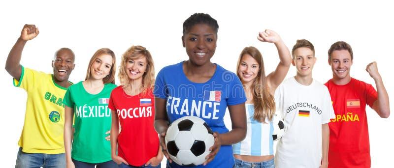 Fan féminin du football français avec la boule et fans d'autres pays photo stock