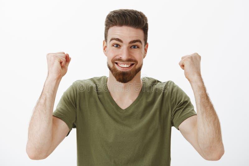 Fan maschio sveglio attivo allegro e stimolato con la barba in maglietta che alza i pugni chiusi nella vittoria e nel trionfo fotografia stock