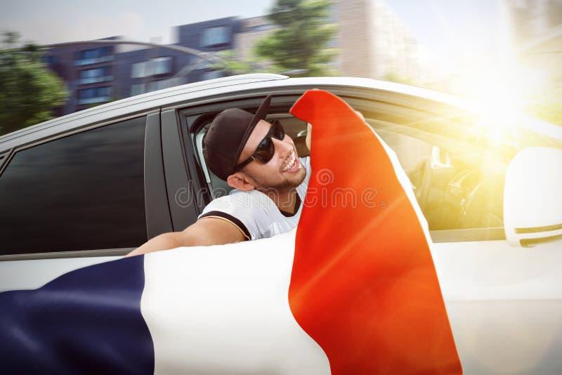 Fan que agita la bandera francesa de una ventanilla del coche fotografía de archivo