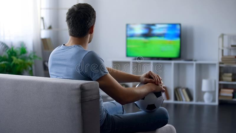 Fan of soccer team watching game on tv home, thinking about match result. Stock photo stock photos
