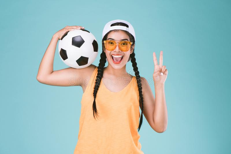 Fan sport woman smiling and happy, holding a soccer ball,celebrating point two finger up second sign royalty free stock photos