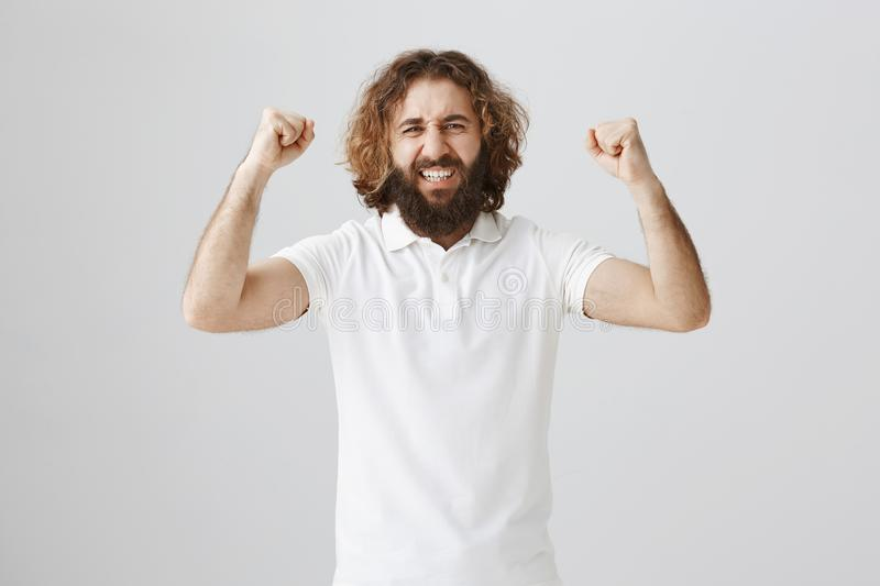 Fan supporting his team on tribune. Portrait of charming mature guy with long beard and messy curly hair raising royalty free stock image