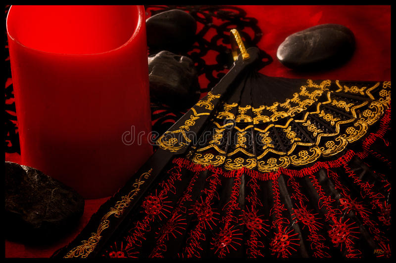Fan-tastic in Red. A black & red based image of a candle, stones, and a fan stock photos