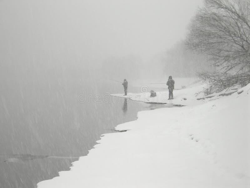 Fanatische Angler, die in den schweren Schneefällen fischen stockfoto