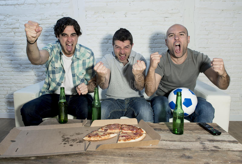 Fanatiska fotbollsfan för vänner som håller ögonen på leken på tv som firar målet som skriker galet lyckligt royaltyfri bild