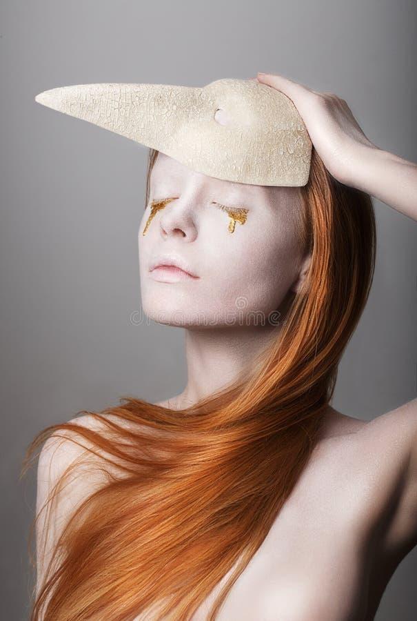 Fanatsy. Stilisierte Frau mit den goldenen Tränen, die Karnevals-Maske halten stockfotos