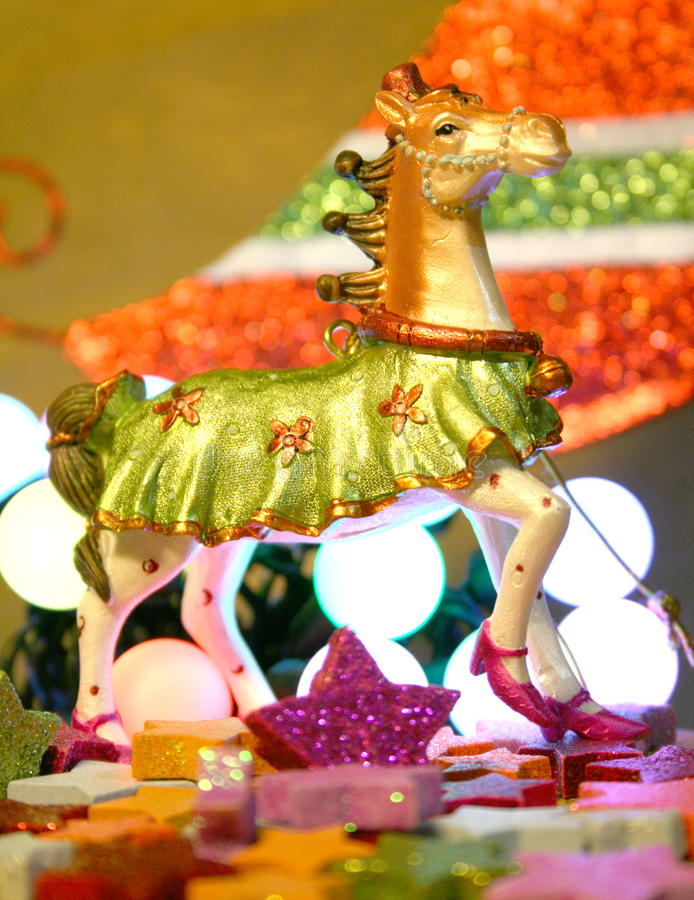 Fancy Christmas Horse. Fancy Fairground Christmas horse between colorfull stars and in fornt of a colored tree royalty free stock photos