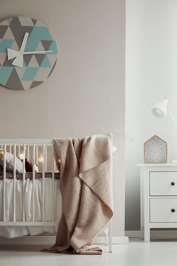 Fancy clack on the wall of elegant baby bedroom interior with white wooden crib with pastel pink blanket and cotton ball lights. Fancy clack on the wall of royalty free stock images