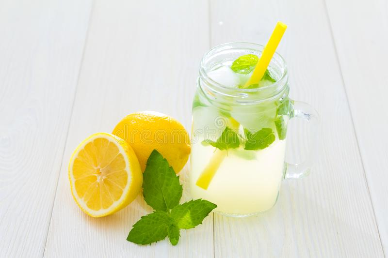 Fancy cool glass of lemonade with ice and mint, Mason jar style cup with yellow straw, green leaves of fresh mint and lemons, one. Of lemon cut in half royalty free stock photography