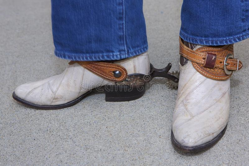 Fancy Cowboy in Spurs. Shin-down,blue-jeaned legs over white cowboy boots with impressive western spurs and leather.  Subject faces forward with one foot stock photo