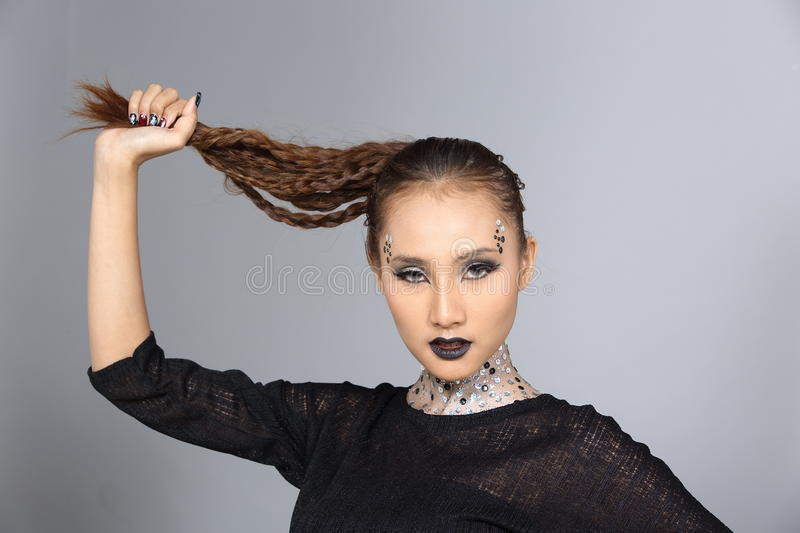 Fancy Creative Talent Make up and Hair style on Asian Beautiful. Model, Black dress hair up costume, silver glitter on neck and pia, studio lighting gray stock photography