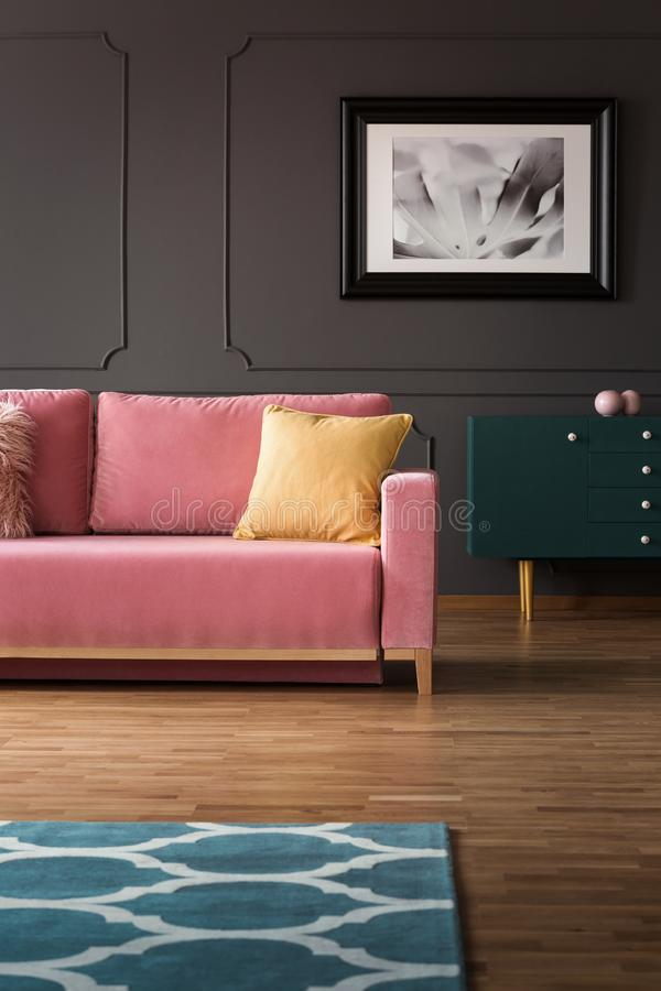Fancy dresser with golden elements and a velvet pink sofa on hardwood floor in a vintage living room interior with gray walls. Rea stock photography