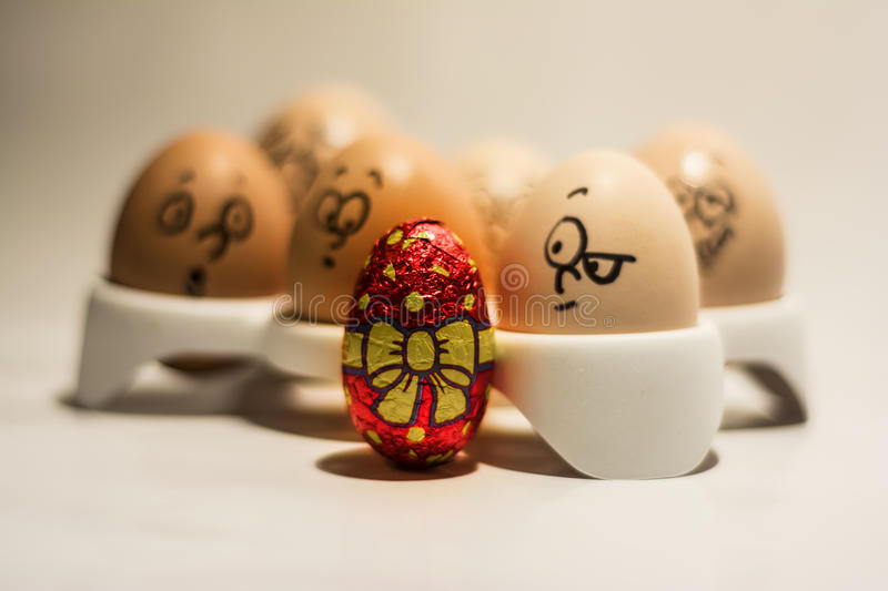 Fancy Easter egg and curious normal eggs. Dressed up Easter egg in front of a pack of normal eggs with various expressions on their faces royalty free stock image