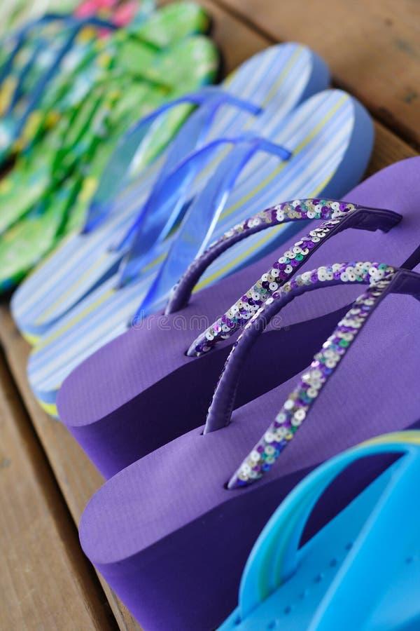 Fancy Flip Flops. Shot of fancy flip flops lined up on a wooden deck during the summer stock photo