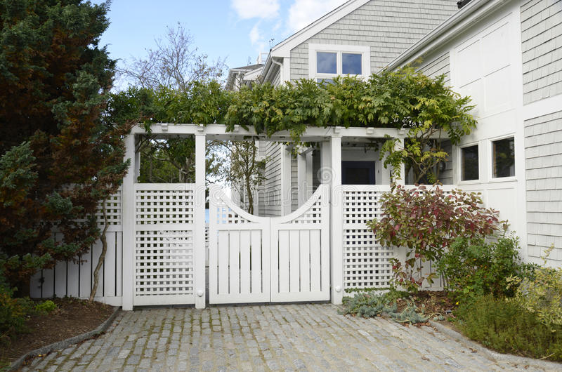 Fancy garden gate. Fancy white garden gate by a shingle house stock images