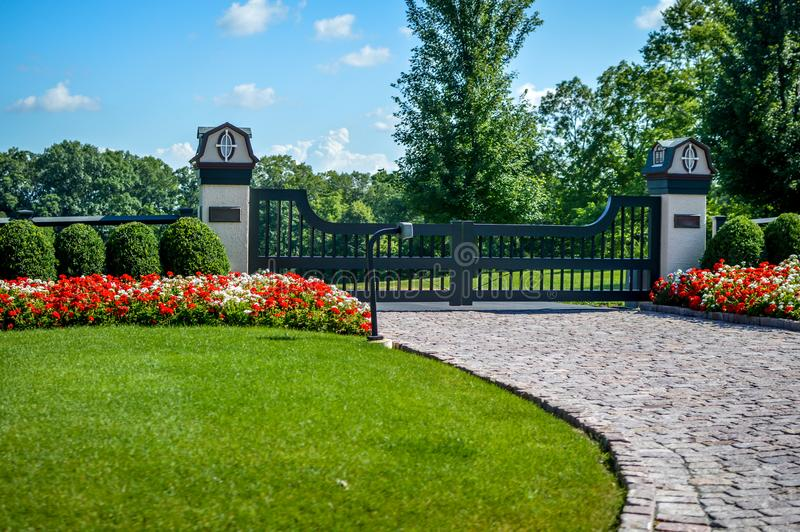 Fancy Gated Entrance Brick Driveway. A fancy gated entrance to a brick driveway with manicured lawn and beautiful flower growing in front of a meticulous royalty free stock photography