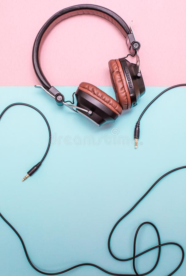 Fancy headphones laying on a flat pink and blue surface. Analog wire frames the layout. Fancy headphones laying on a flat pink and blue surface. Analog wire stock photos