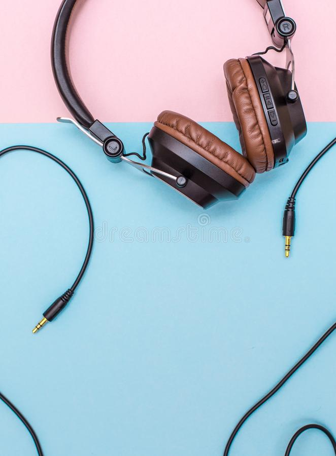 Fancy headphones laying on a flat pink and blue surface. Analog wire frames the layout. Fancy headphones laying on a flat pink and blue surface. Analog wire stock image