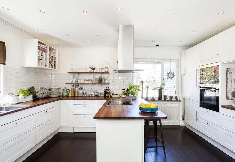 Fancy kitchen interior with wooden counter top and dar wooden floor white cupboards stock photography