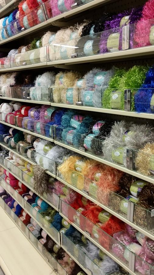 Fancy Knitting Yarn. Shelves at a craft store filled with colorful sparkling yarn for knitting and sewing stock images