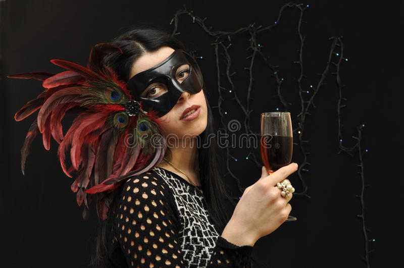 Fancy mask lady with vine glass stock image