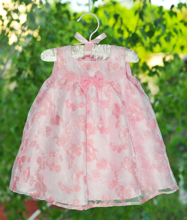 Fancy pink dress hanging on hangers on the background of the window. stock image