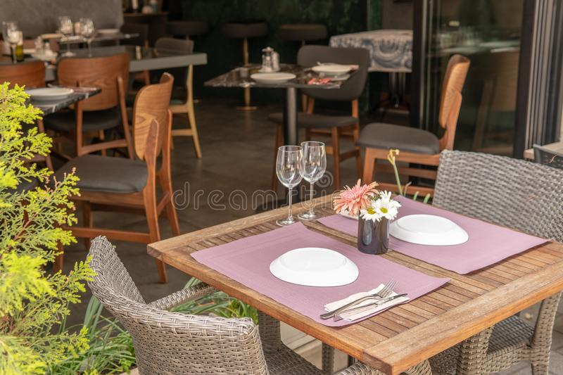 Fancy set table with flowers outside hotel. Outside table set with plate settings and flowers in the center, dinner, food, home, hotel, nature, party, restaurant stock photography