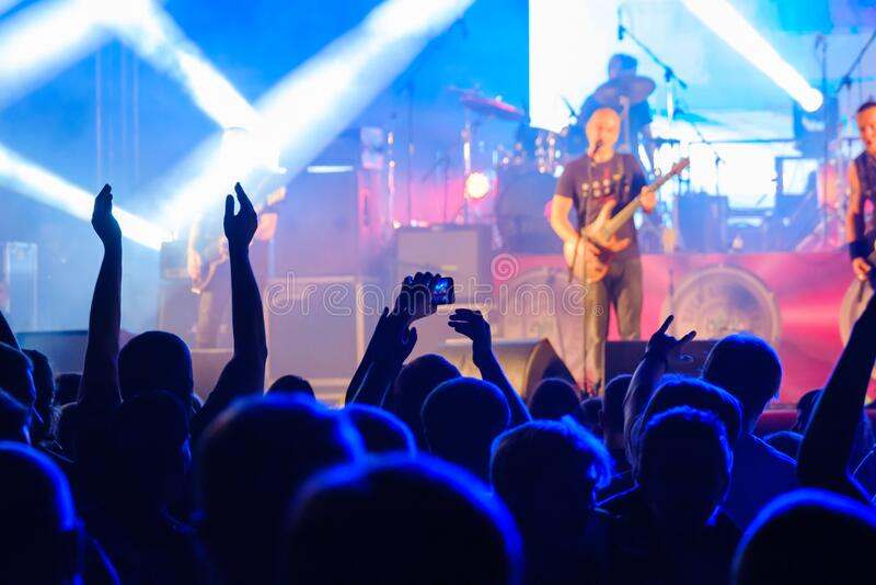Faner som lyssnar på rockband på scenen royaltyfri foto