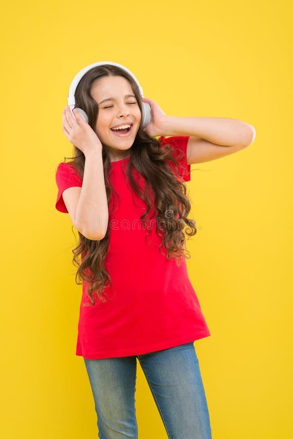 Fangen Sie den Rhythmus Kind oder jugendlich genie?en die Musik, die in den Kopfh?rern spielt Wenig M?dchen, das ihre Lieblingsmu stockbilder