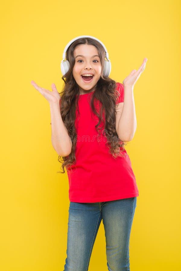 Fangen Sie den Rhythmus Wenig M?dchen, das ihre Lieblingsmusik genie?t Kinderhörende Musikkopfhörer Musik geschlagenes Konzept stockbild