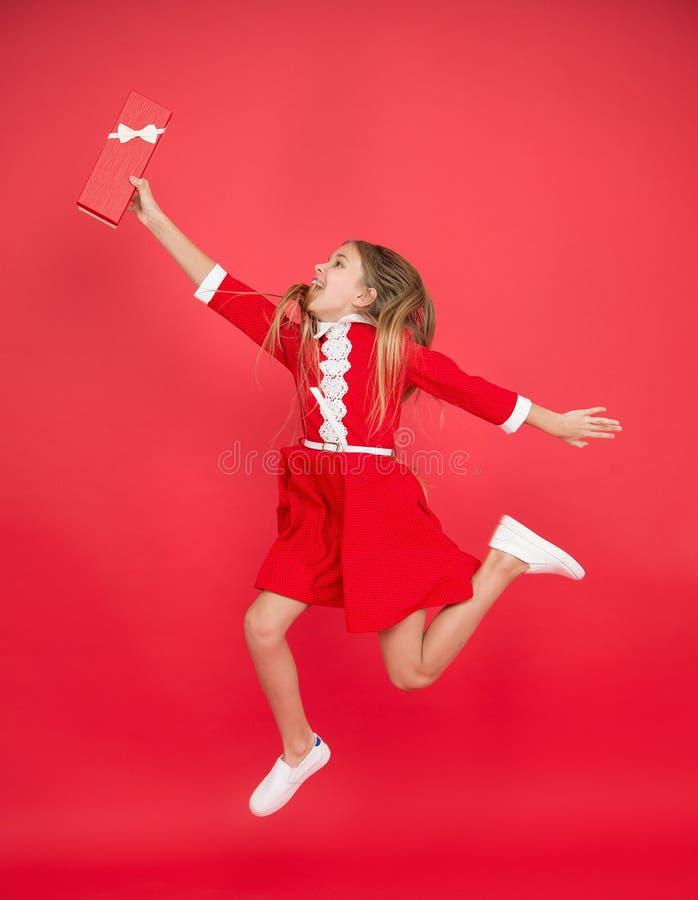 Fangen Sie es Glückliches Kind springen für Geschenkbox Geburtstagsmädchenlächeln mit Geschenk in der Bewegung Mädchen feiern Fei stockfotos