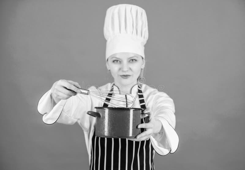 Fangen Sie, peitschende an oder schlagende Creme langsam zu wischen Gebrauchshandschneebesen Schlagsahnespitzen und -tricks Fraue stockfotografie