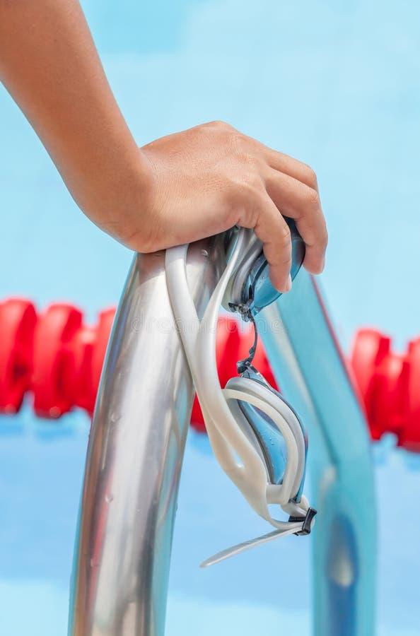 Fangen Sie an, Rennkonzept mit Nahaufnahme zu schwimmen das Handzupacken auf Leiter lizenzfreies stockfoto