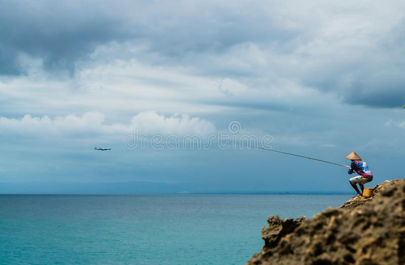 Fangende Fische des Fischers auf dem Felsen lizenzfreies stockbild
