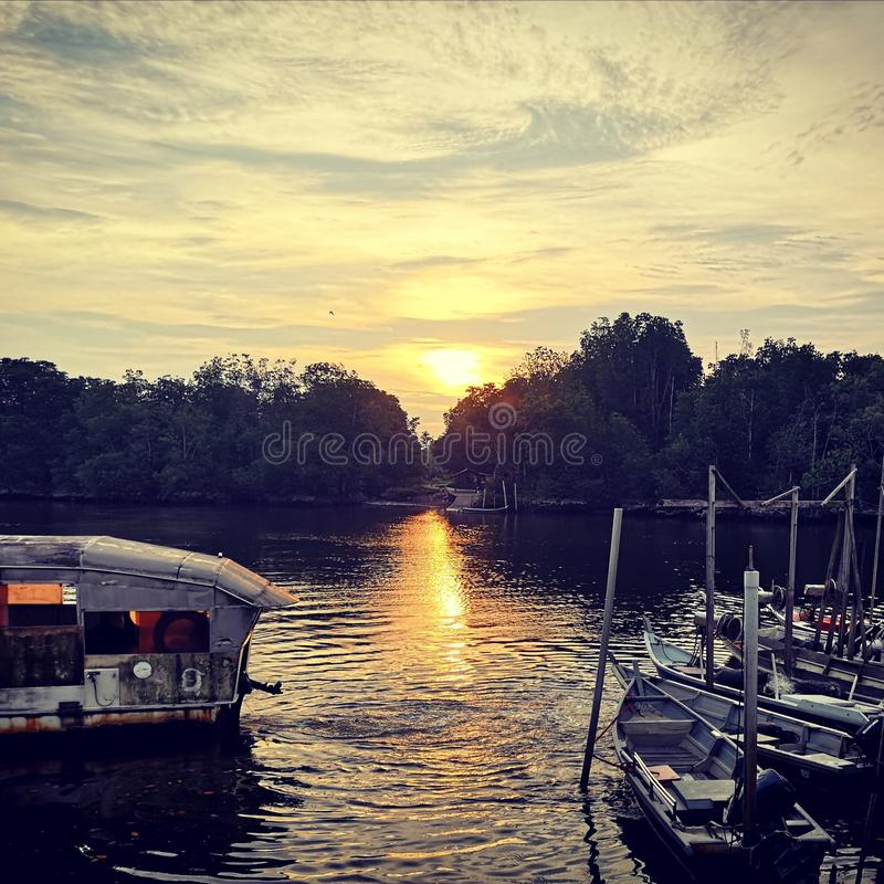 Fangende Sonnenuntergangzeit der Fische an einem Sonntag Abend am Flussufer lizenzfreie stockfotografie